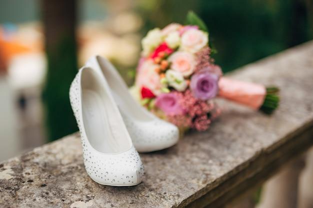 Les chaussures de la mariée se trouvent sur l'herbe verte