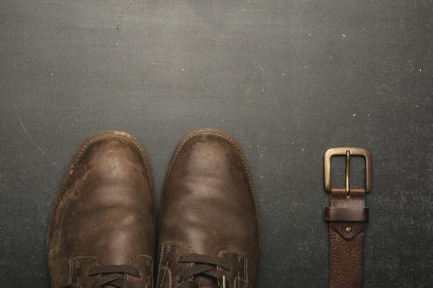 Chaussures marron classiques et ceinture sur table en bois.