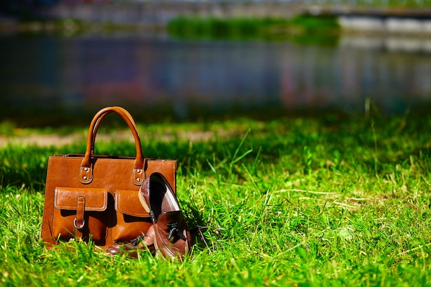 Chaussures marron rétro et sac en cuir pour homme en herbe d'été aux couleurs vives dans le parc
