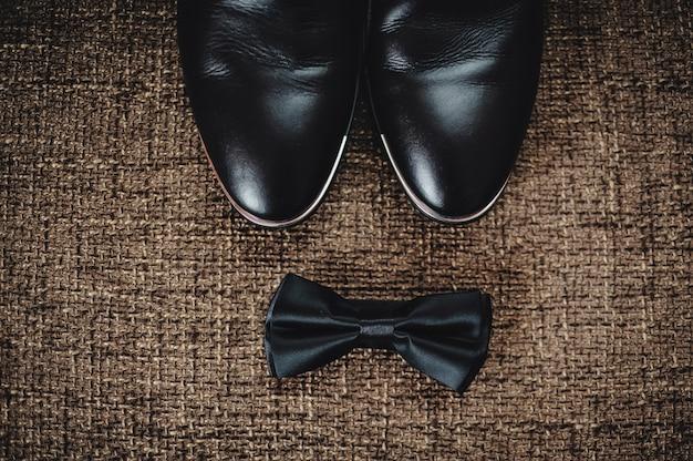 Des chaussures noires et un papillon noir reposent sur un sac marron