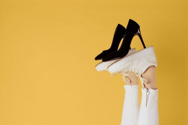 Chaussures noires pour femmes sur fond jaune jambes inversées