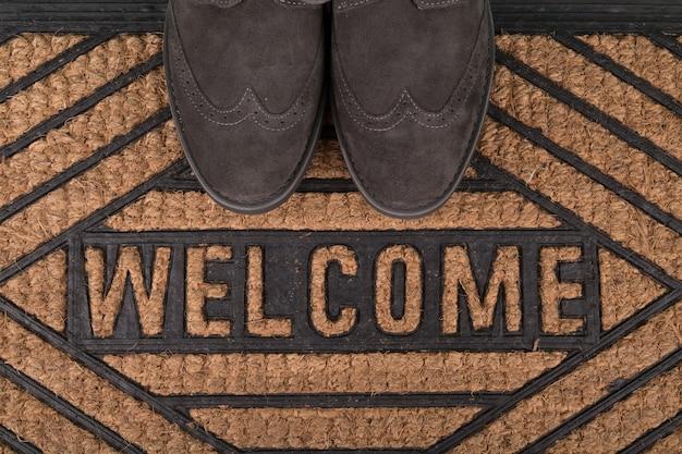 Chaussures sur nouveau paillasson de bienvenue sur plancher en bois