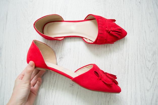 Chaussures ouvertes rouges dans une main féminine. bois clair. vue de dessus