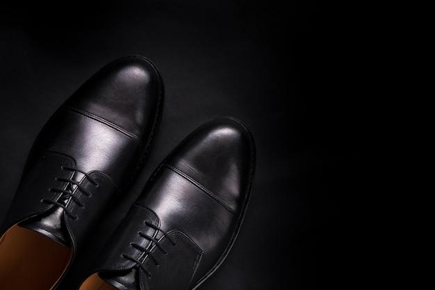 Chaussures oxford noires sur fond noir. vue de dessus. copiez l'espace.