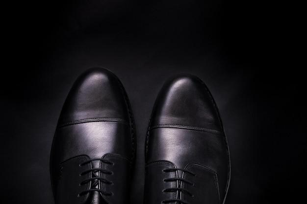 Chaussures oxford noires sur fond noir.