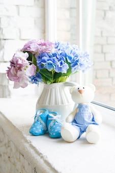 Chaussures pour enfants bleues avec un lièvre jouet et un bouquet de fleurs bleues sur le rebord de la fenêtre