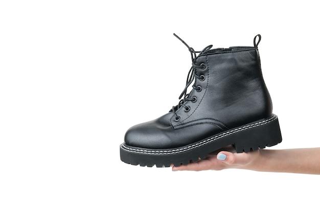 Chaussures pour femmes brutales noires dans la main d'une femme isolée sur une surface blanche