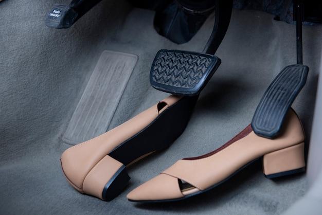 Chaussures pour femmes placées sous les pédales de frein et d'accélérateur de la voiture.