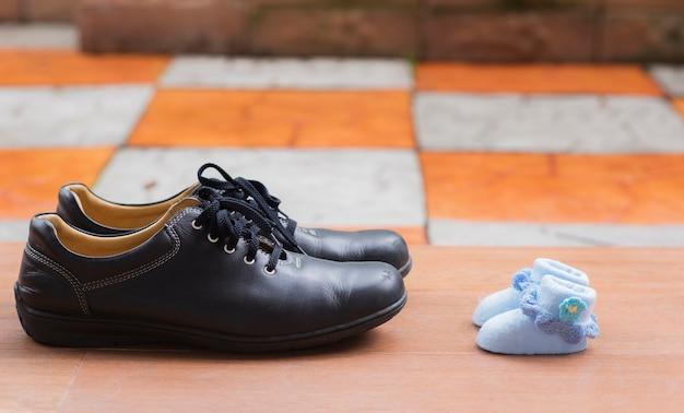 Chaussures pour hommes en face des chaussures pour bébés