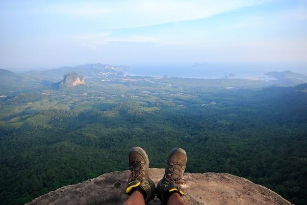 Chaussures pour hommes sur la falaise il y a une vue au-dessous de la forêt.