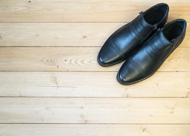Chaussures pour hommes noires en cuir sur un plancher en bois.