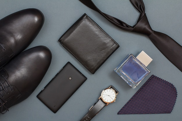 Chaussures pour hommes noirs, téléphone portable, sac à main en cuir, montre avec un bracelet en cuir noir, eau de cologne pour hommes, mouchoir et cravate sur fond gris. accessoires pour hommes. vue de dessus