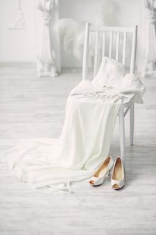 Chaussures et robe de mariée sur chaise dans la chambre