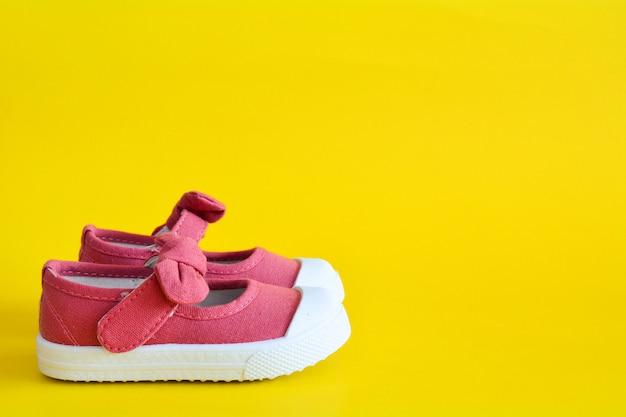 Chaussures roses pour enfants sur jaune.