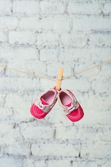 Chaussures rouges bébé sur une corde contre un mur de briques blanches