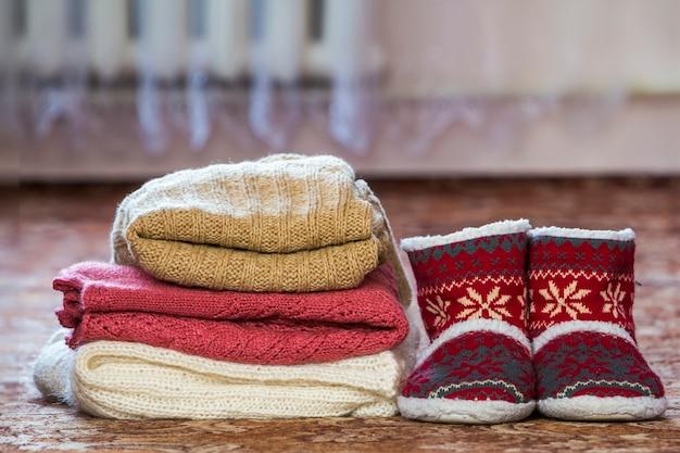 Chaussures rouges avec des bottes de nouvel an et une pile de chandails tricotés