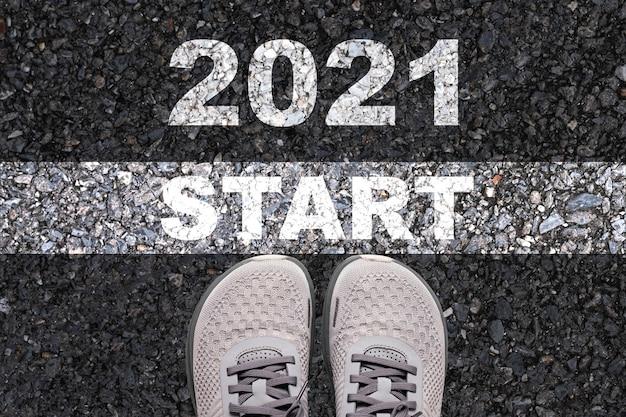 Chaussures sur route avec des mots peints de début et 2021
