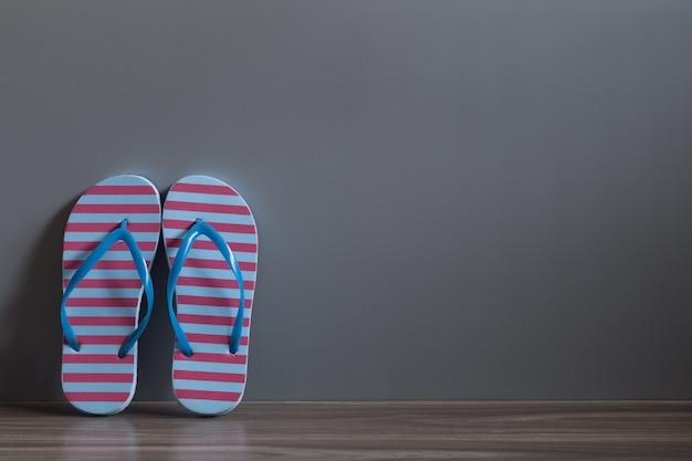 Chaussures de sandale rouge et bleu sur le plancher de bois contre le mur gris.