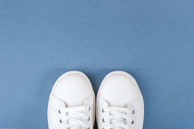 Chaussures de sport blanches, baskets avec lacets sur bleu