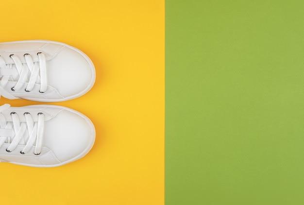 Chaussures de sport blanches, baskets à lacets sur fond vert et jaune
