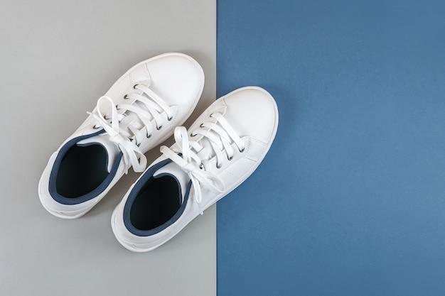 Chaussures de sport blanches, baskets à lacets sur gris bleu