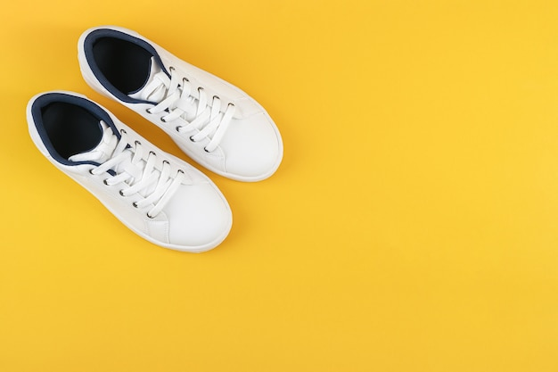 Chaussures de sport blanches, baskets avec lacets sur jaune