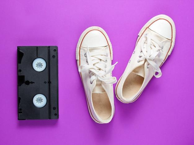 Chaussures de sport blanches rétro, bande vidéo sur fond violet