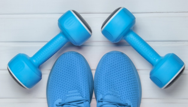 Chaussures de sport bleues pour l'entraînement, haltères sur parquet blanc. vue de dessus.