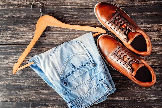 Chaussures de sport en cuir marron et jeans sur la vue de dessus en bois sombre. concept de mode