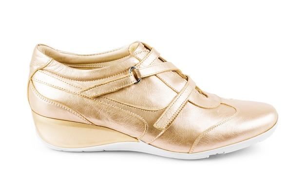 Chaussures de sport dorées isolées sur fond blanc