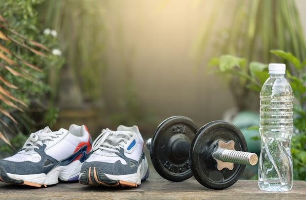Chaussures de sport avec des haltères et une bouteille sur un arbre flou. métaphore fitness et concept d'entraînement, exercice d'un style de vie sain