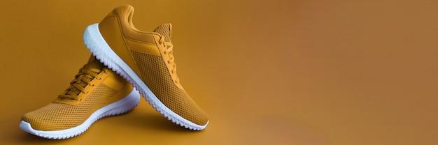 Chaussures de sport sur mur de couleur moutarde