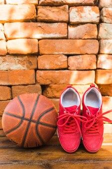 Chaussures de sport rouges et basketball contre pile de mur de briques