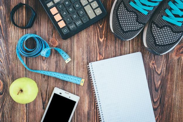 Chaussures de sport, smartphone, bande, calculatrice, bracelet de remise en forme, pomme verte et ordinateur portable sur fond de bois