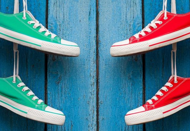 Chaussures de sport en textile suspendues à un mur bleu