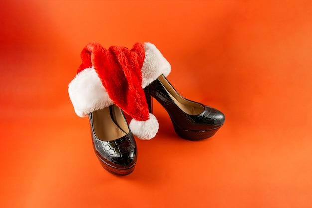 Chaussures à talons avec un bonnet de noel sur fond rouge
