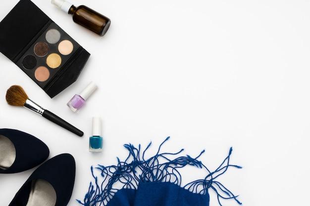 Chaussures à talons hauts bleues, palette cosmétique, pinceau, vernis à ongles et écharpe bleue