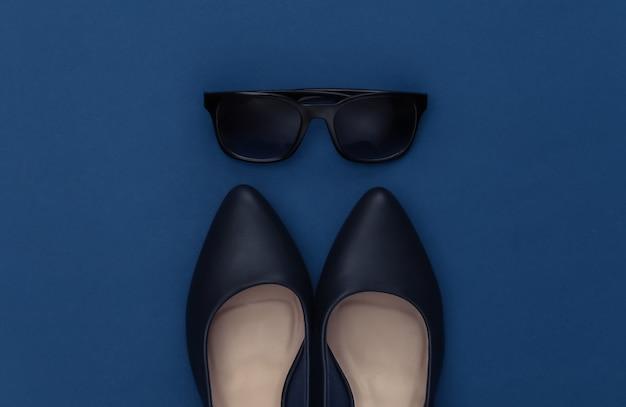 Chaussures à talons hauts en cuir à la mode et lunettes de soleil sur fond bleu classique. couleur 2020. vue de dessus.