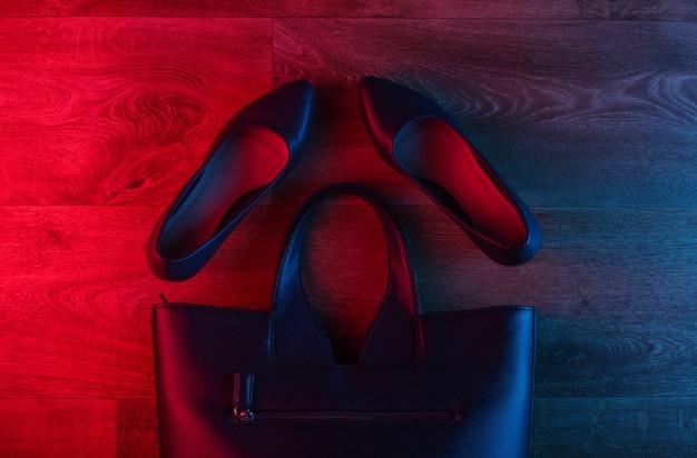 Chaussures à talons hauts en cuir et sac sur plancher en bois avec une lueur dégradé rouge-bleu néon