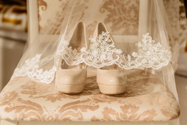 Chaussures à talons hauts pour mariage heureux sous voile sur la chaise