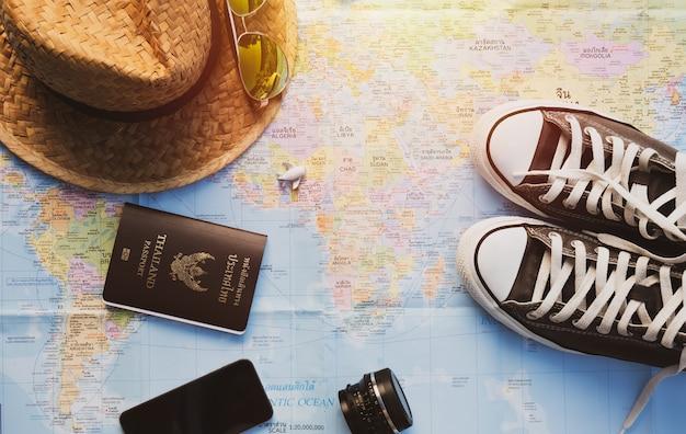 Chaussures, téléphone intelligent, objectif, avion, chapeau de paille et passeport sur carte avec effet de lumière solaire.