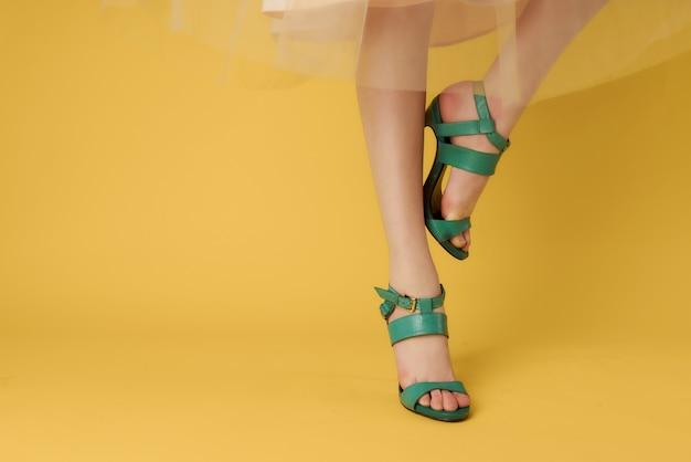 Chaussures vertes sur les jambes des femmes posant fond jaune gros plan