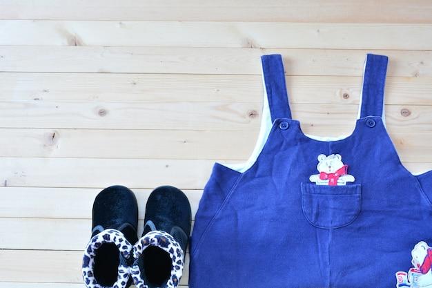 Chaussures et vêtements de bébé ou enfant sur la vue de dessus de table en bois sous la lumière de la nature