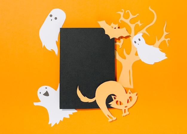 Chauve-souris et chat sur un morceau de papier avec arbre derrière et fantômes lévitant près de
