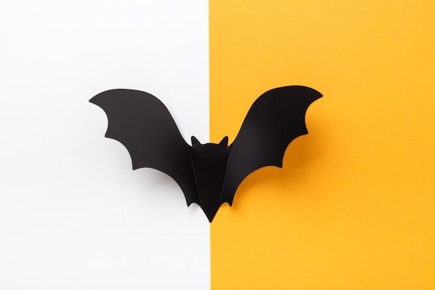 Chauve-souris en papier noir sur fond jaune et blanc. notion d'halloween. mise à plat, vue de dessus, espace de copie - image