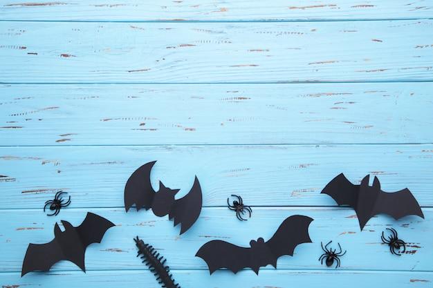 Chauves-souris de papier halloween avec des araignées sur un fond en bois bleu. halloween