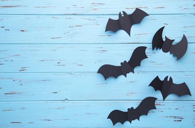 Chauves-souris de papier d'halloween sur un fond en bois bleu. halloween, cadre
