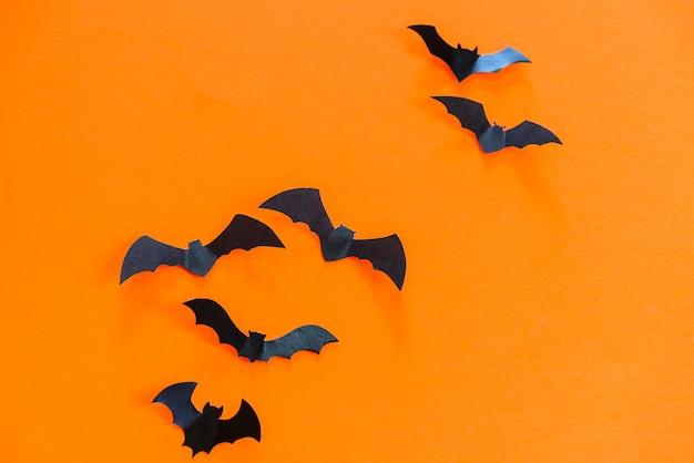 Chauves-souris en papier noir volant sur fond orange.