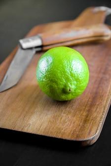 Chaux et vieux couteau de poche traditionnel sur une planche à découper en bois