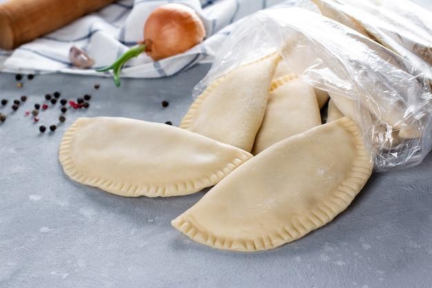 Chebureks congelés dans le sac sur table grise avec des ingrédients